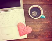 Laptop or notebook with cup of coffee and origami heart on old wooden table toned with a retro vint poster