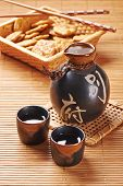 picture of shot glasses  - Japanese Sake set from a bottle and two shot glasses on a bamboo mat - JPG