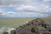 image of dike  - Clouds and storm over a dike in a lake - JPG