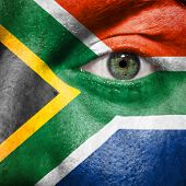 stock photo of afrikaner  - Flag painted on face with green eye to show South Africa support in sport matches - JPG