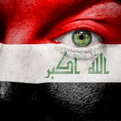 stock photo of iraq  - Flag painted on face with green eye to show Iraq support - JPG
