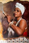 image of graffiti  - Woman in Aruba wearing a head scarf and traditional jewellery smoking a big fat Cuban cigar with a look of relish and defiance against an old grunge graffiti painted brown wall - JPG