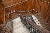 picture of bannister  - Winding interior staircase with wood paneling on the walls and an ornate wrought iron and oak bannister viewed looking down the treads from above - JPG