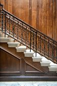 stock photo of bannister  - Flight of old ornate interior stairs with a decorative wrought iron bannister and wood paneling on the walls - JPG