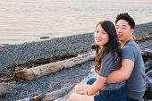 stock photo of driftwood  - Young cute Asian American couples sitting on driftwood on beach - JPG