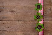 stock photo of red clover  - Wooden background with red and white checkered ribbon and green clovers for a happy new year - JPG