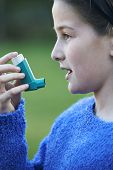 stock photo of asthma  - Girl Using Inhaler To Treat Asthma Attack - JPG