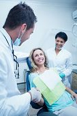 picture of dentist  - Male dentist with assistant shaking hands with woman in the dentists chair - JPG