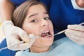 stock photo of pediatrics  - Pediatric dentist using dental explorer and angled mirror in mouth open of a patient - JPG