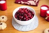 stock photo of berries  - Red berry jam with cookies and red candles on knitted cloth on wooden table shallow depth of field focus on top berries - JPG