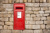 stock photo of old post office  - traditional old fashioned English red postbox mounted in a cotswold stone wall - JPG