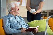 foto of retirement age  - Elderly happy man reading the book and his tea time - JPG