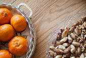 stock photo of satsuma  - closeup photo of a glass plate full of nuts and a dish of citrus fruit