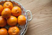 pic of satsuma  - bright orange citruce fruit in a traditional dish on a wooden table - JPG
