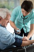stock photo of hypertensive  - Young attractive nurse checking the elderly man - JPG