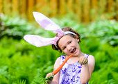 image of bunny ears  - A young girl wearing Easter bunny ears holds a fresh carrot in her hand while posing like a bunny outside in a lush garden setting during the spring season - JPG