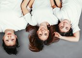 image of three sisters  - Three teenage sisters lying on the floor and smiling - JPG