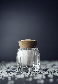 stock photo of salt shaker  - Rustic salt shaker over black wooden table with salt all over it - JPG