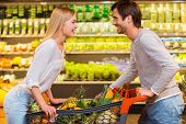 pic of grocery cart  - Cheerful young couple leaning at the shopping cart and looking at each other while shopping in a food store - JPG