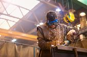 picture of goggles  - Young man with protective goggles welding in a factory - JPG