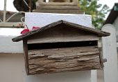 stock photo of mailbox  - Old wooden mailbox house shape placed on white wall background - JPG