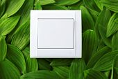 stock photo of toggle switch  - Light switch on green leaves background - JPG