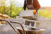 picture of wheelbarrow  - Bricklayer taking another brick from a wheelbarrow - JPG