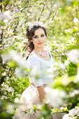 stock photo of japan girl  - Portrait of beautiful girl posing outdoor with flowers of the cherry trees in blossom during a bright spring day - JPG