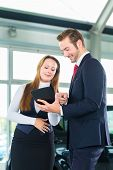 stock photo of showrooms  - Seller or car salesman and female client or customer in car dealership presenting the interior decoration of new and used cars in the showroom on tablet computer - JPG