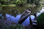 picture of old boat  - Two old wooden row boats at the shore during the day - JPG