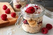 pic of breakfast  - Healthy breakfast overnight oats with fresh raspberries and shredded coconut in a glass jar - JPG