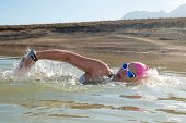foto of swimming  - An active female is seen swimming across a dam while wearing a pink swimming cap - JPG