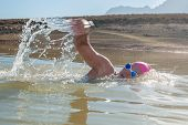 image of swimming  - An active female is seen swimming across a dam while wearing a pink swimming cap - JPG