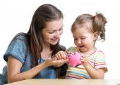 picture of coin bank  - Mother and daughter kid putting coins into piggy bank - JPG