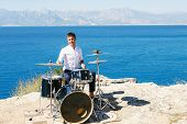 stock photo of drum-kit  - Young handsome guy in a white shirt drummer sitting behind the drum kit outdoors and unseat him the sea and beautiful sky - JPG