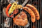 foto of grilled sausage  - Pork chop steak and vegetable with sausage on a flaming BBQ grill - JPG