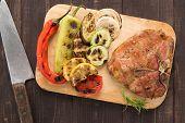 stock photo of pork chop  - Grilled pork chop and vegetables on wooden background - JPG