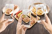 foto of pork chop  - friends using smartphones to take photos of sausage and pork chop and french fries - JPG