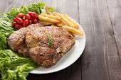 image of pork chop  - grilled pork chop steak and vegetables with french fries on wooden background - JPG