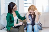 foto of psychologist  - Psychologist comforting a depressed patient in the office - JPG