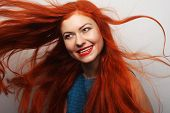 stock photo of flowing hair  - Beautiful young happy woman with long flowing red hair - JPG