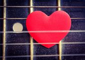 foto of heart sounds  - A red love heart in the strings of a guitar - JPG