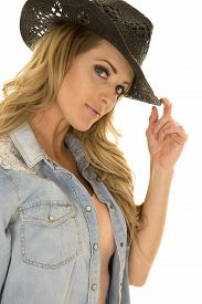 stock photo of cowgirls  - A close up of a cowgirl in her jean shirt and western hat - JPG
