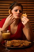 stock photo of bing  - Young lady having a late night binge of cookies and milk - JPG
