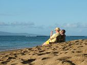 stock photo of elderly couple  - view of an elderly couple on cell phones relaxing on a beach - JPG