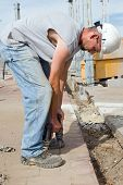 pic of bend over  - Construction electrician bending over to drill pavement - JPG