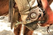 foto of christian cross  - Spurs on a cowboy boot in a stirrup