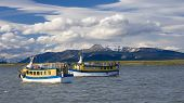 Boats waiting for tourists on the Patagonian lake poster