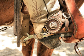 image of christian cross  - Spurs on a cowboy boot in a stirrup  - JPG