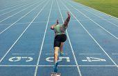 Sprinter Taking Off From Starting Block On Running Track poster